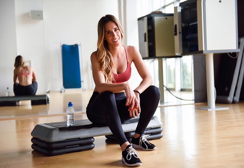 Mujer joven en ropa deportiva sosteniendo una manzana en el gimnasio