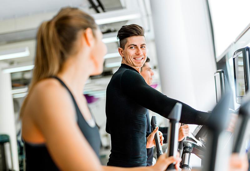 guapo Hombre y hermosa joven Mujer el Uso un paso a paso en un gimnasio
